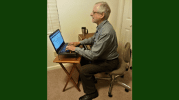 Larry Johnson, the editor and publisher of the Cobb County Courier seated in an office chair in front of a small table with a laptop in article about Cobb County Courier Meet the Editor