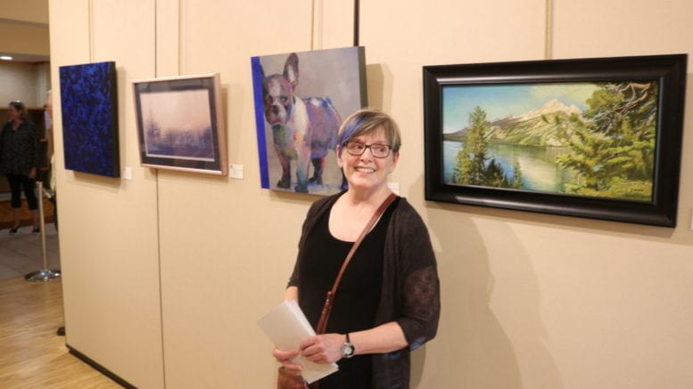NancyJeanette Long smiling in front of her prizewinning painting, a portrait of a stocky dog with upright ears looking ahead skeptically