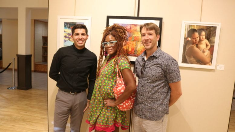 Artists Isaac Alcantar, Tokie Rome-Taylor, and Miles Davis in front of a painting by Alcantar
