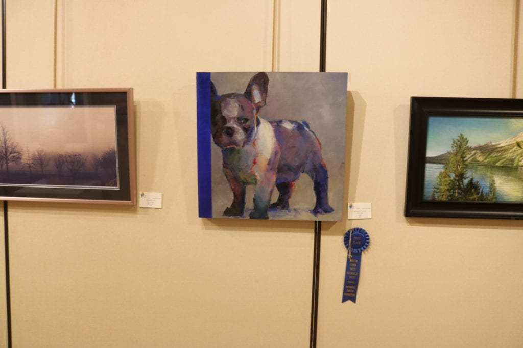 """Grand Prize entry """"French Blue,"""" by NancyJeanette Long. The painting is of a stocky dog with large upright ears staring ahead with a skeptical expression. The painting has a significant amount of the color blue."""