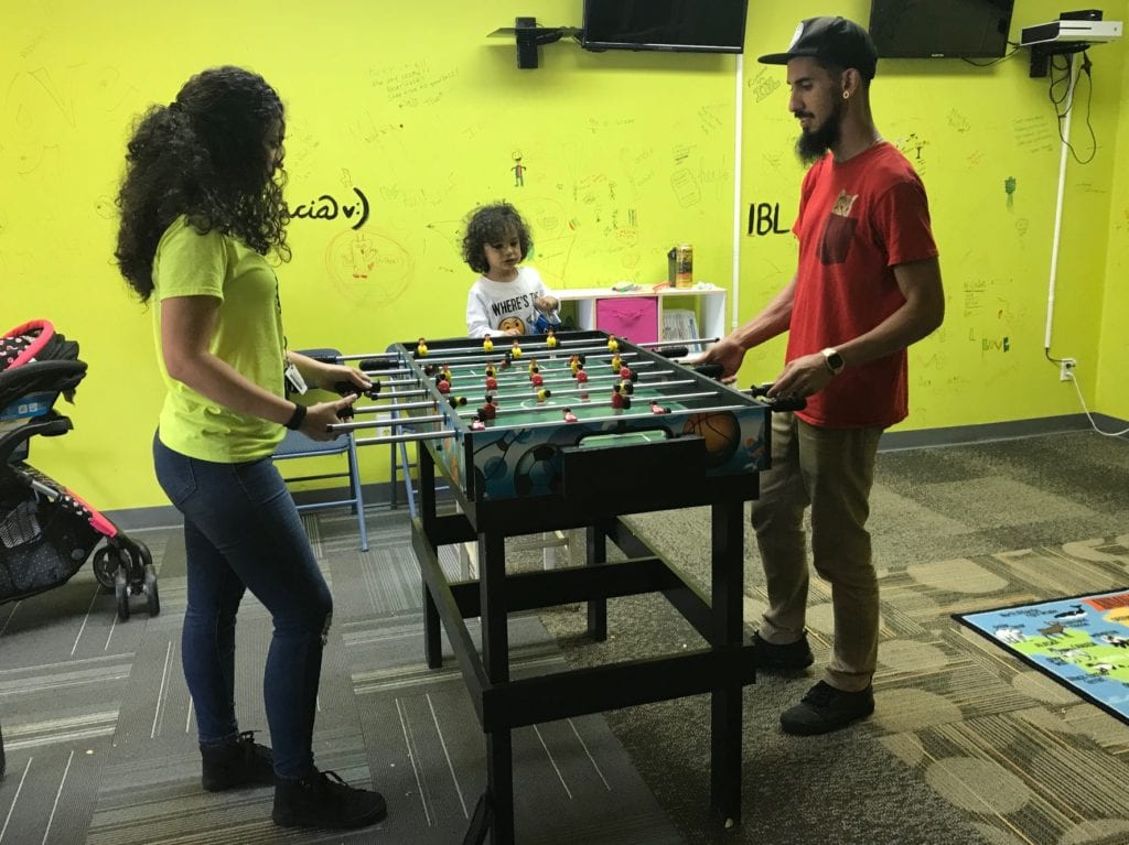 Inspired by Lewis volunteer Celina Gonzalez and Jaymi Rios played foosball while son Julian watched. (photo by Rebecca Gaunt)