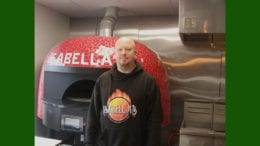 Carlos Bickers, the owner of Isabella's Pizza and Wings in front of his pizza oven (photo by Larry Felton Johnson)
