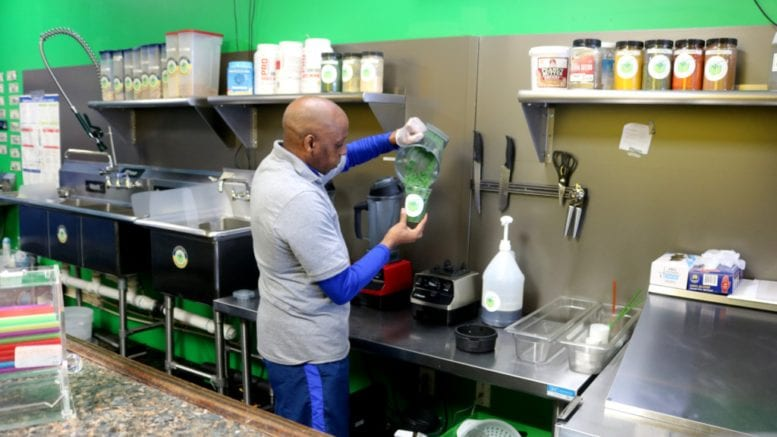 Ron Bolden, owner of Paradise Smoothie Juice Bar, mixes a Green Forest (photo by Larry Felton Johnson)