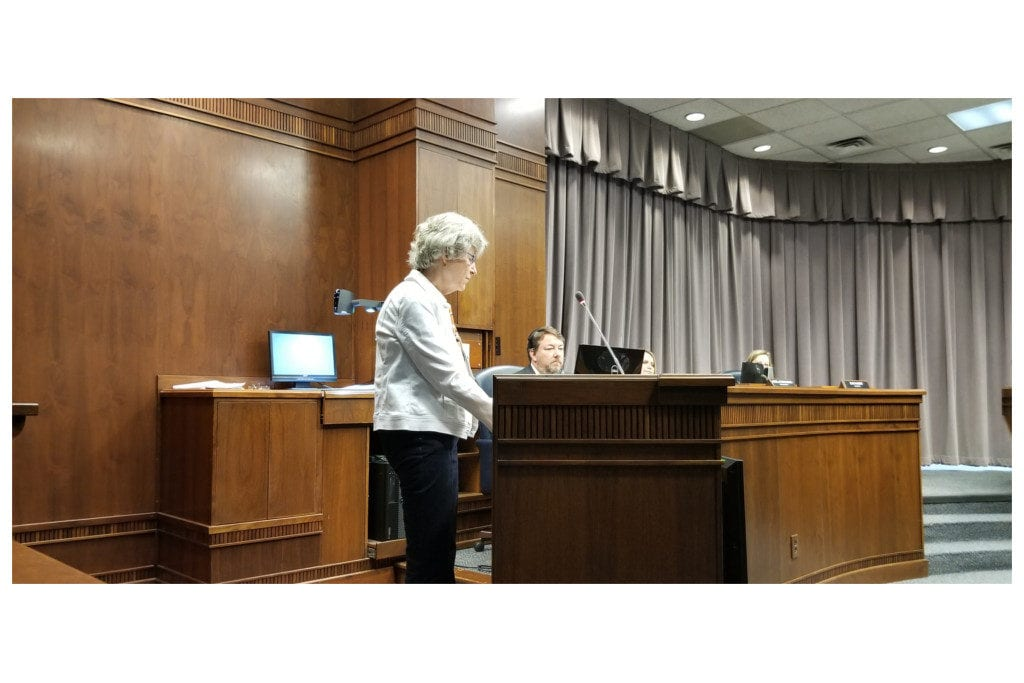 Robin Meyer at lectern at Board of Commissioners meeting.