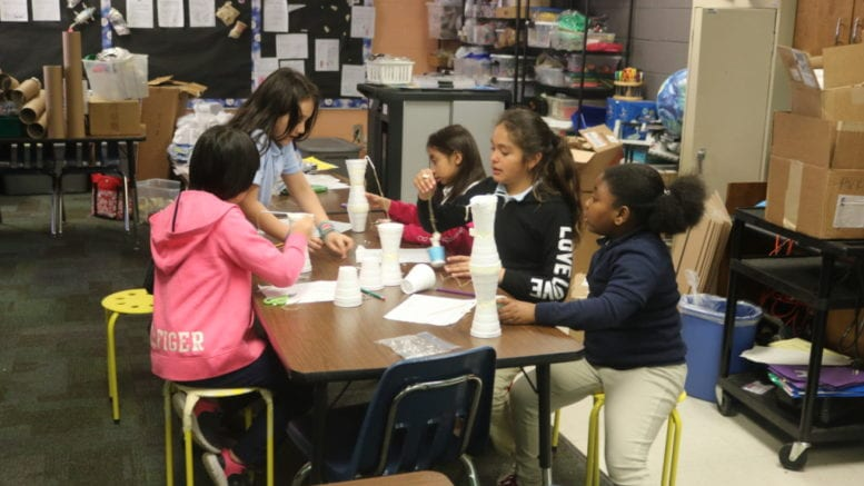 Children around a table building cranes from styrofoam and other common materials for a STEM project.