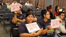 Immigrants rights advocates hold up signs calling for the defunding of 287-G