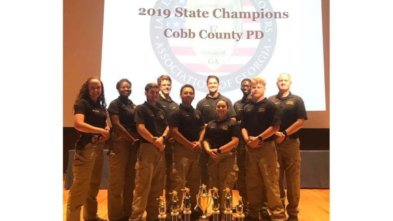 Cobb Police Explorers display trophies from their 11th consecutive state championship