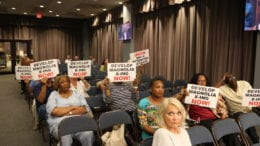 South Cobb residents hold up signs calling for the redevelopment of the long-vacant site of the former Magnolia Crossing apartment complex (photo by Larry Felton Johnson)