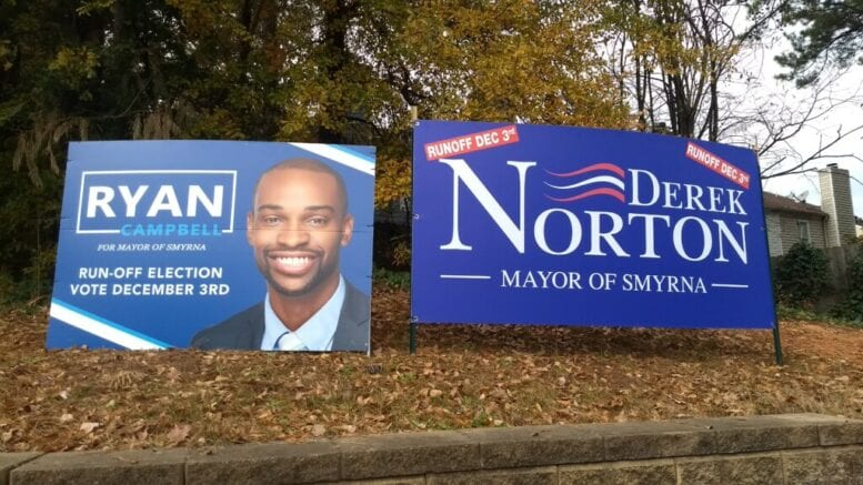 Campaign signs for Ryan Campbell and Derek Norton with the article about Smyrna mayor contributions for the December 3 runoff