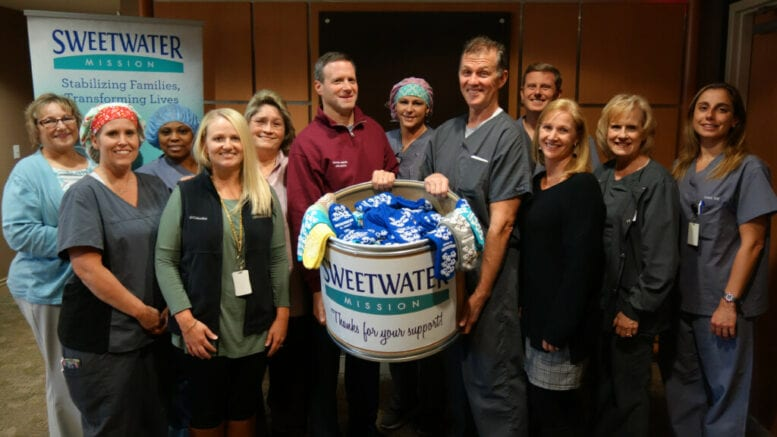 Group photo with sock donation box from Sweetwater Mission