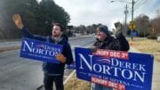 Two men waving Derek Norton signs on Spring Road in article Derek Norton wins