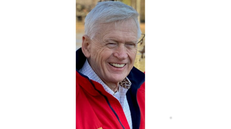 Larry Davage, smiling, in red jacket