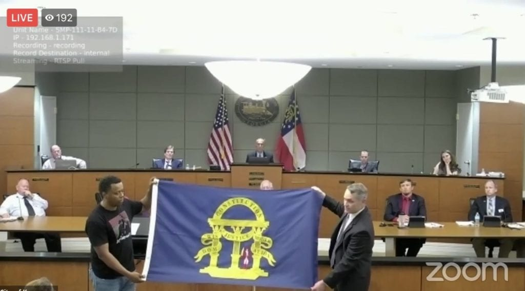 Former Councilman Jimmy Dickens and Rep. Ed Setzler display the historically-accurate replacement flag.