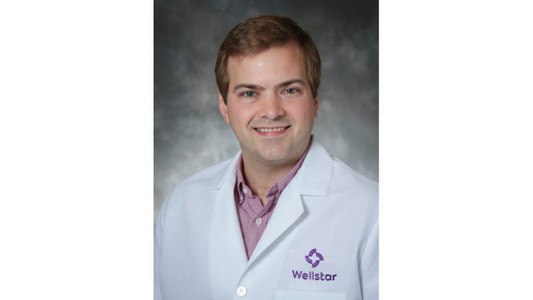 Dr. Jonathan Peeples, Wellstars Director of Telepsychiatry in lab coat with Wellstar logo