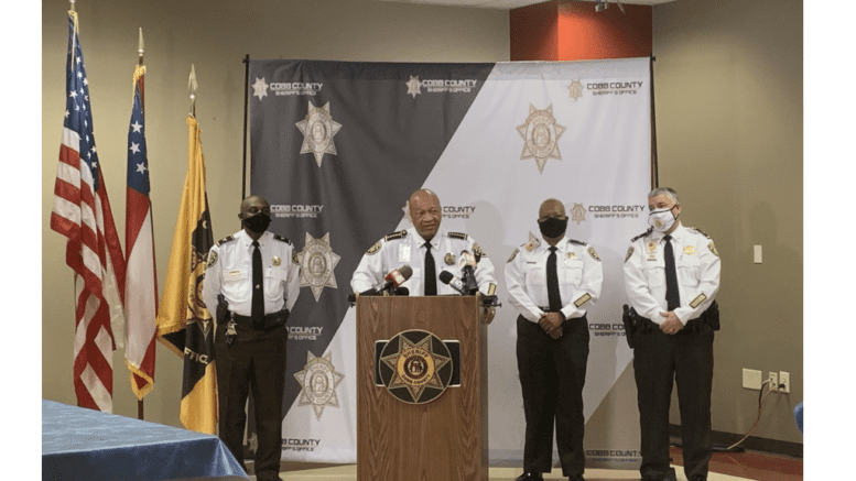 Sheriff Craig Owens and part of his command staff announce major reforms to the Cobb sheriff's office. Pictured from left to right: Col. Temetris Atkins, Sheriff Craig Owens, Chief Deputy Rhonda Anderson and Maj. Steven Gaynor all wearing dress white shirts surrounding lectern
