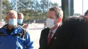 Governor Brian Kemp wearing a mask speaking to reporters