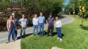 (From l-r) Nikkie Grzelka, John Huey, Ron Gaynor, Michael Thornton, Brad Grzelka, Eugene Williams and Diane Downs hope the most recent accident at this curve will bring much needed safety improvements to Pete Shaw Road.