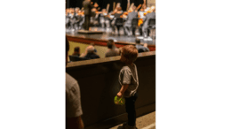 child watching orchestra from balcony