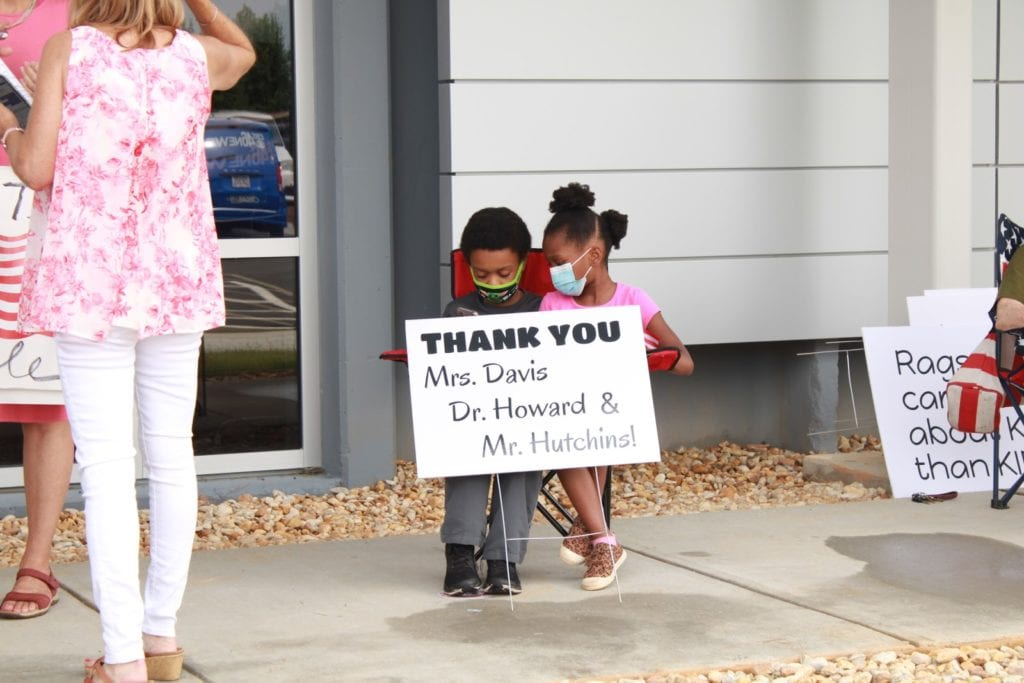 Two children holding sign with thanks to the three Black school board members