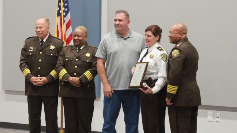 Sheriff Craig Owens, Chief Deputy Rhonda Anderson and Assistant Chief Deputy Michael Register promote Amie Garrett, with her husband looking on (photo by Arielle Robinson)