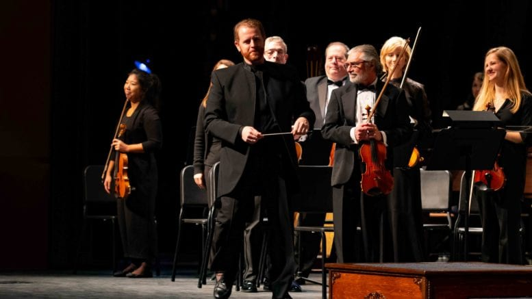 Music Director and Conductor Timothy Verville (pictured, standing center) leads the Georgia Symphony Orchestra's return to live performances in its upcoming 71st concert season