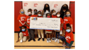 Group of girls dressed in Girls Inc t-shirts holding giant check to advance social and racial equity