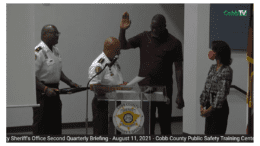 Dominique Wilkins, hand raised, as Sheriff Craig Owens swears him in