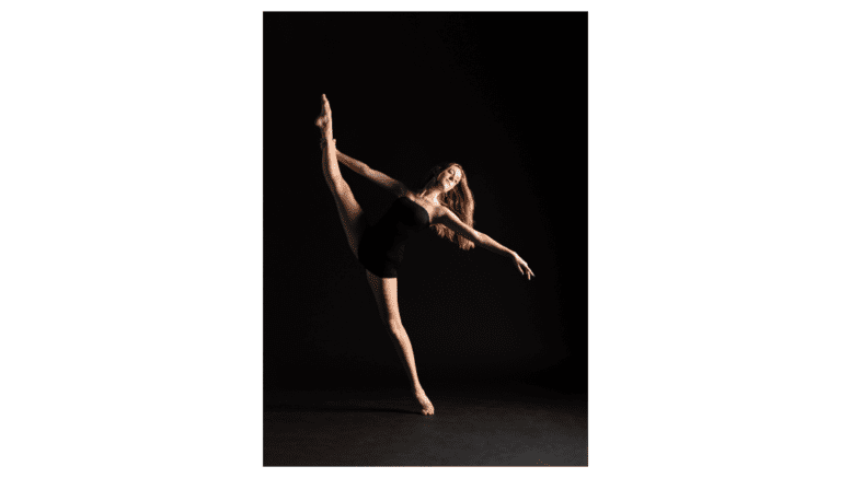 Woman dancing, doing extended kick with arm behind high extended leg
