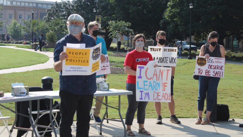 Group of people in front of table holding signs in favor of mask mandate at KSU