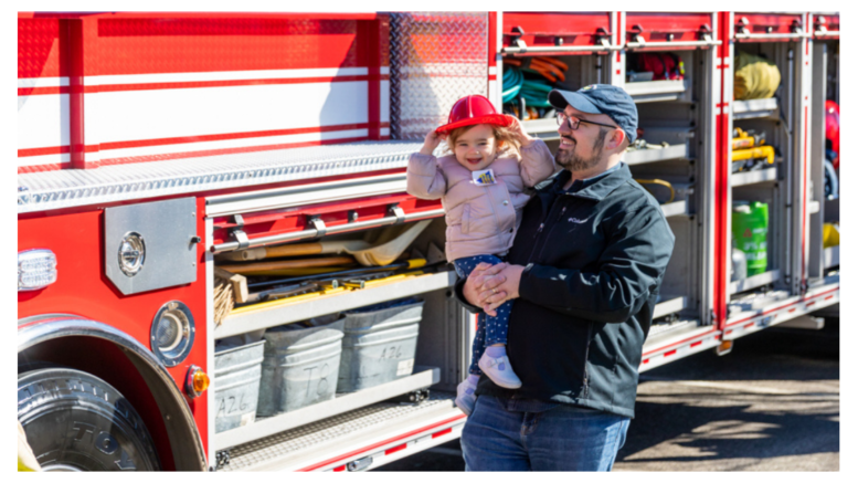 Photo of man holding child by fire truck