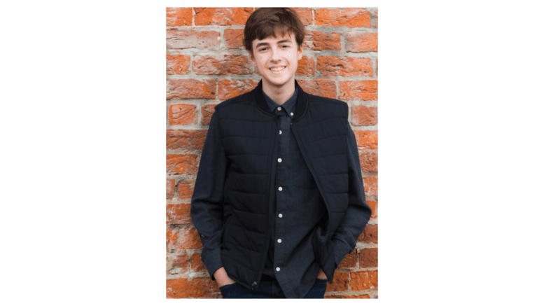 Student musician and composer Will Weaver standing against brick wall